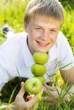 Muchacho adolescente sonriente lindo con las manzanas verdes Imágenes de archivo libres de regalías