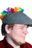 Muchacho adolescente sonriente que desgasta el casquillo plano y las flores Imagen de archivo libre de regalías