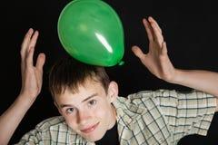 Muchacho adolescente sonriente que juega con el globo verde claro Foto de archivo