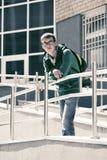 Muchacho adolescente triste con la mochila contra una construcción de escuelas Imagenes de archivo