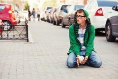 Muchacho adolescente triste en la depresión que se sienta en calle de la ciudad Imagen de archivo