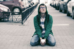 Muchacho adolescente triste en la depresión que se sienta en la acera Foto de archivo libre de regalías