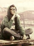 Muchacho adolescente triste en la depresión que se sienta en la acera en calle de la ciudad Foto de archivo