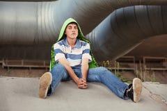 Muchacho adolescente triste en la depresión que se sienta en la tierra Imagen de archivo