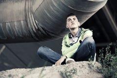 Muchacho adolescente triste en la depresión que se sienta en la tierra Foto de archivo libre de regalías
