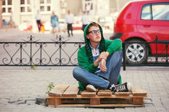 Muchacho adolescente triste en una sudadera con capucha que se sienta en la acera Imágenes de archivo libres de regalías