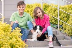 Muchacho adolescente y muchacha que juegan con el perrito Foto de archivo libre de regalías