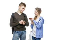 Muchacho adolescente y muchacha que se colocan con los teléfonos móviles Fotografía de archivo libre de regalías