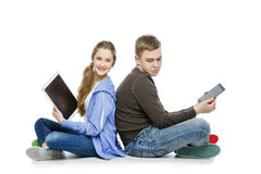 Muchacho adolescente y muchacha que se sientan con las tabletas Imagen de archivo libre de regalías