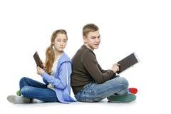 Muchacho adolescente y muchacha que se sientan con las tabletas Imágenes de archivo libres de regalías