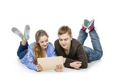 Muchacho adolescente y muchacha que se sientan con las tabletas Foto de archivo libre de regalías