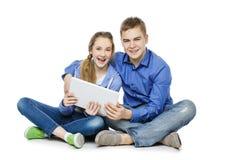 Muchacho adolescente y muchacha que se sientan con las tabletas Fotografía de archivo