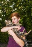 Muchacho adolescente y su gato de gato atigrado afuera en el jardín Imagenes de archivo