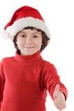Muchacho adorable con el sombrero rojo de la Navidad que dice OK. Foto de archivo libre de regalías