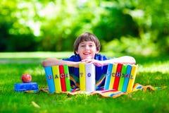 Muchacho adorable del estudiante que se relaja en libros de lectura del patio de escuela Fotos de archivo