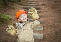 Muchacho adorable del niño con los guantes grandes que juegan a la manitas Outside Imágenes de archivo libres de regalías