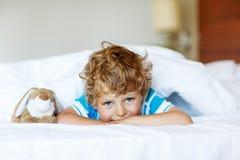 Muchacho adorable del niño después de dormir en su cama blanca con el juguete Fotografía de archivo