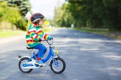 Muchacho adorable del niño en casco rojo y el impermeable colorido que montan el suyo Foto de archivo