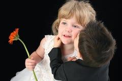 Muchacho adorable del niño que besa a la muchacha de cuatro años en mejilla foto de archivo