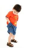 Muchacho adorable del niño que controla los bolsillos para saber si hay dinero imagen de archivo