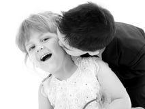 Muchacho adorable del niño que da a muchacha bonita de cuatro años un beso Imágenes de archivo libres de regalías