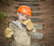 Muchacho adorable del niño con los guantes grandes que juegan a la manitas Outside Foto de archivo libre de regalías
