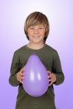 Muchacho adorable del preadolescente con un globo púrpura Fotos de archivo