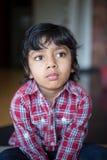 Muchacho adorable en el niño comprobado de la camisa que mira fijamente con el foco y la atención Imagen de archivo