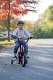 Muchacho adorable en el parque, con su bici, aprendiendo montar imagen de archivo libre de regalías