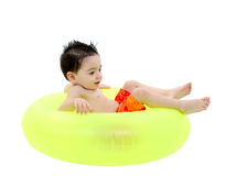 Muchacho adorable en el traje de baño que se sienta en tubo interno verde sobre blanco Imagenes de archivo