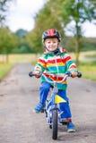 Muchacho adorable feliz del niño en casco de seguridad en la bici Foto de archivo libre de regalías