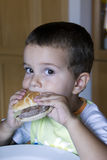 Muchacho adorable que come el cheeseburger Imagen de archivo
