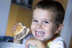Muchacho adorable que come el cheeseburger Foto de archivo libre de regalías
