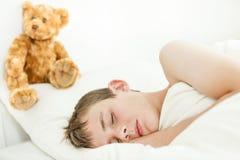 Muchacho adorable que duerme con el oso de la felpa Imagen de archivo