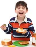 Muchacho adorable que hace el emparedado de la manteca de cacahuete Imagenes de archivo