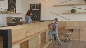 Muchacho adorable que hace orden a la camarera en cafetería almacen de metraje de vídeo