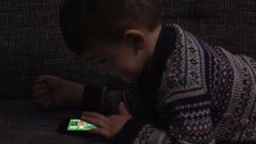 Muchacho adorable que se sienta en el sofá en la sala de estar y que juega con el artilugio Niño que aprende cómo utilizar smartp