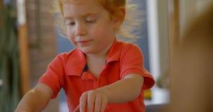 Muchacho adorable que tiene comida dulce en casa 4k almacen de metraje de vídeo
