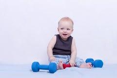 Muchacho adorable sonriente de 10 meses que se sienta con pesas de gimnasia y la mirada del hombre de la cámara fotografía de archivo