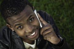 Muchacho africano en el teléfono celular afuera Fotografía de archivo libre de regalías