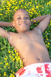 Muchacho africano que miente en la hierba Fotografía de archivo