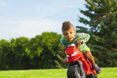 Muchacho afro lindo en el juguete rojo de la moto Imagen de archivo libre de regalías