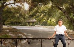 Muchacho afroamericano negro feliz que se sienta en la puerta del hierro Foto de archivo