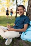 Muchacho afroamericano que estudia en parque Imágenes de archivo libres de regalías