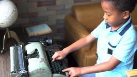 Muchacho afroamericano que mecanografía en la máquina de escribir en sala de estar metrajes