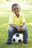 Muchacho afroamericano que se sienta en fútbol en parque Fotos de archivo