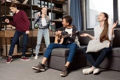 Muchacho afroamericano que toca la guitarra acustic mientras que sus amigos que bailan detrás en casa Foto de archivo