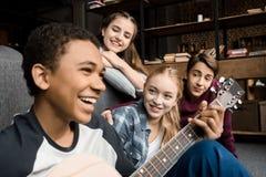 Muchacho afroamericano que toca la guitarra acustic mientras que sus amigos que escuchan en casa foto de archivo libre de regalías