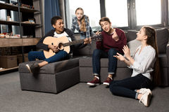 Muchacho afroamericano que toca la guitarra acustic mientras que sus amigos que escuchan y que cantan en casa Foto de archivo