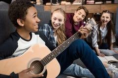Muchacho afroamericano que toca la guitarra acustic y que canta mientras que sus amigos que escuchan en casa Imagenes de archivo